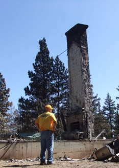 DR Chaplain praying at the remains of a home destroyed by wildfire in central WA state.